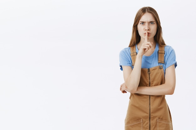 Jeune femme en colère chutant et fronçant les sourcils dérangé, besoin de silence, faire un geste chut