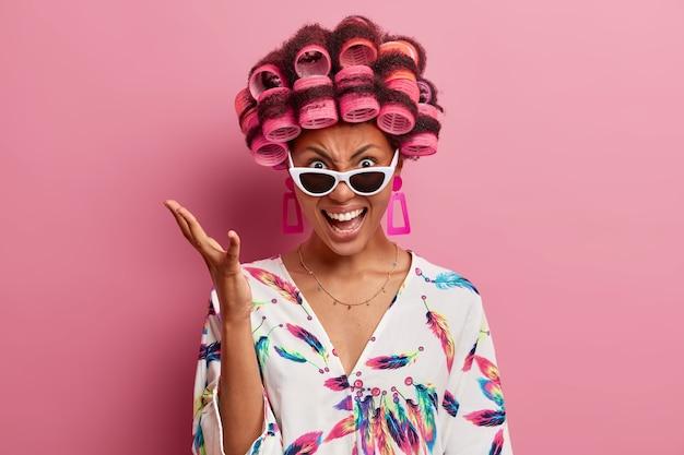 Jeune femme en colère crie avec émotion et gestes avec une expression irritée, porte des bigoudis pour faire une coiffure frisée, vêtue d'une robe de chambre décontractée et de lunettes de soleil, isolée sur un mur rose