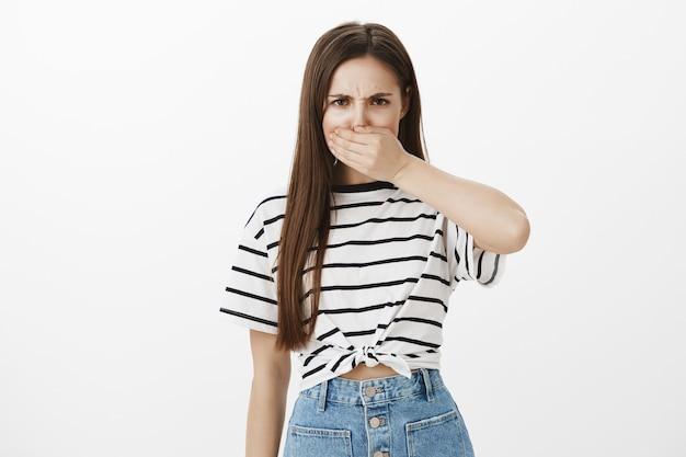 Jeune femme en colère ferme la bouche et fronce les sourcils, folle de parler