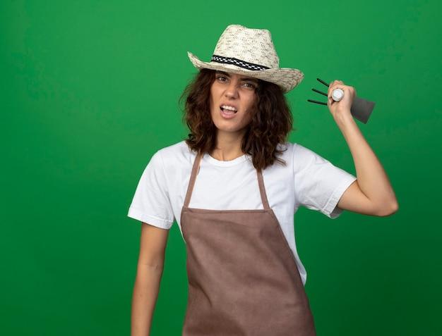 Jeune femme en colère jardinier en uniforme portant chapeau de jardinage soulevant un râteau houe