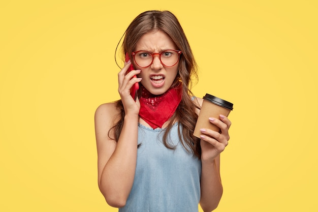 Une jeune femme en colère se sent intense lorsqu'elle a une conversation téléphonique avec un ami, entend des bêtises, n'est pas d'accord avec quelque chose, sourit avec aversion, boit du café, isolée sur un mur jaune.