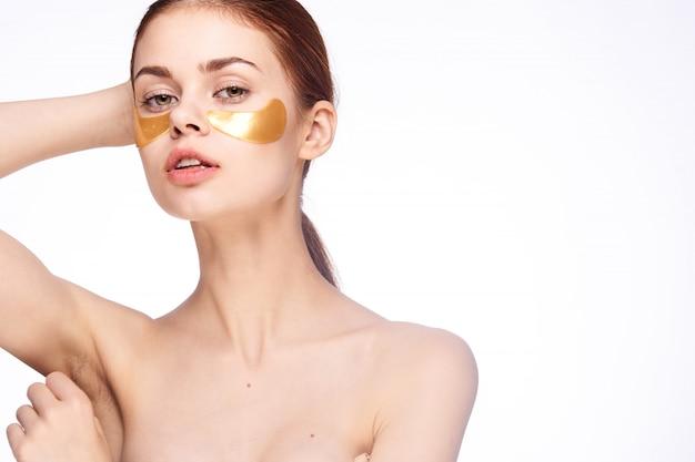 Jeune femme colle des patchs sous les yeux, soins esthétiques à domicile, soins du visage et des yeux