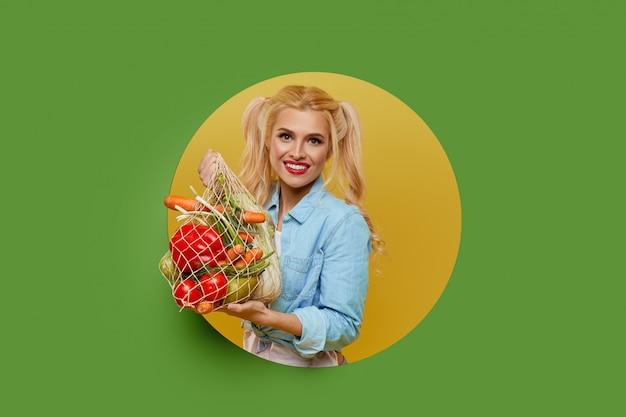 Jeune femme a collecté des légumes frais dans un sac de ficelle sur fond vert. peeks hors d'un trou rond dans le mur.