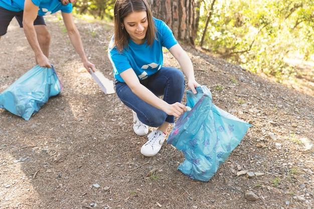 Jeune femme collecte des ordures dans la forêt