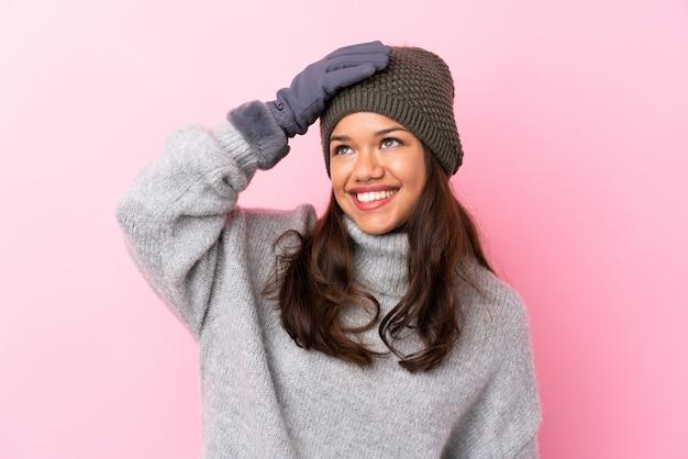 Jeune femme colombienne avec chapeau d'hiver sur mur rose isolé en riant