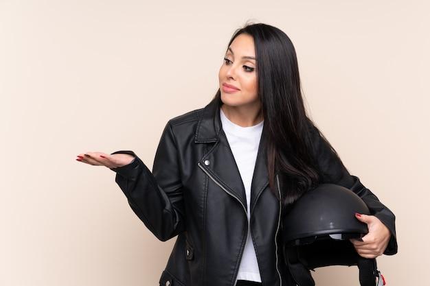 Jeune femme colombienne tenant un casque de moto sur un mur isolé, tendant les mains sur le côté pour inviter à venir