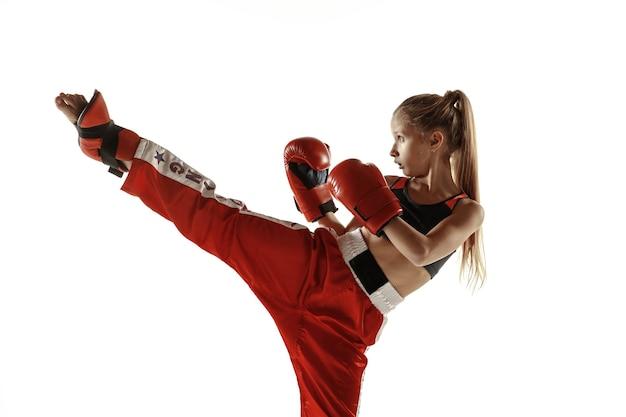 Jeune femme combattant de kickboxing s'entraînant sur blanc