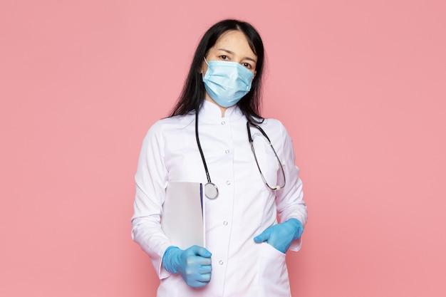 Jeune femme en combinaison médicale blanche gants bleus masque de protection bleu avec stéthoscope sur rose