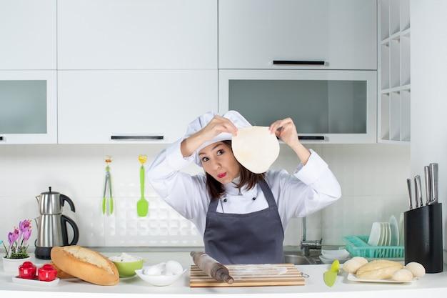 Jeune femme commis chef en uniforme debout derrière table jouant avec son chapeau dans la cuisine blanche