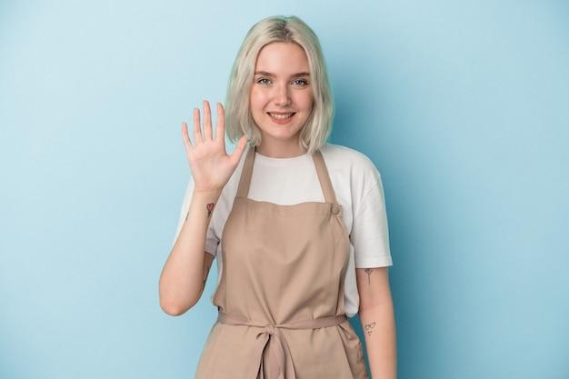 Jeune femme de commis de magasin caucasien isolée sur fond bleu souriante joyeuse montrant le numéro cinq avec les doigts.