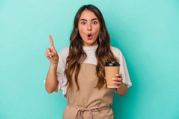 Jeune femme de commis de magasin caucasien tenant un café à emporter isolé sur fond bleu ayant une bonne idée, concept de créativité.