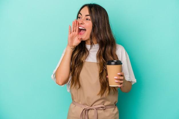 Jeune femme de commis de magasin caucasien tenant un café à emporter isolé sur fond bleu criant et tenant la paume près de la bouche ouverte.