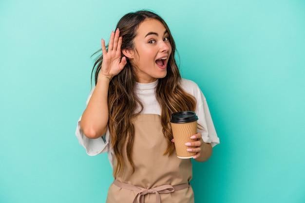 Jeune femme de commis de magasin caucasien tenant un café à emporter isolé sur fond bleu essayant d'écouter un potin.