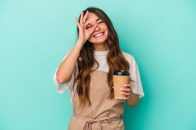 Jeune femme de commis de magasin caucasien tenant un café à emporter isolé sur fond bleu excité en gardant le geste ok sur les yeux.