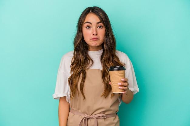 Jeune femme de commis de magasin caucasien tenant un café à emporter isolé sur fond bleu hausse les épaules et ouvre les yeux confus.