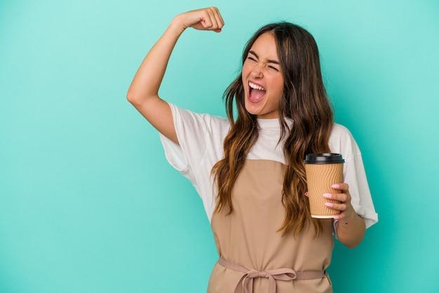 Jeune femme de commis de magasin caucasien tenant un café à emporter isolé sur fond bleu levant le poing après une victoire, concept gagnant.