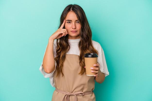 Jeune femme de commis de magasin caucasien tenant un café à emporter isolé sur fond bleu pointant le temple avec le doigt, pensant, concentré sur une tâche.