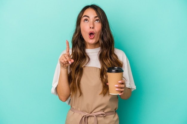 Jeune femme de commis de magasin caucasien tenant un café à emporter isolé sur fond bleu pointant vers le haut avec la bouche ouverte.
