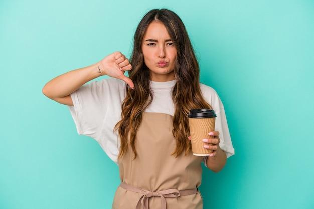 Jeune femme de commis de magasin caucasien tenant un café à emporter isolé sur fond bleu se sent fière et confiante, exemple à suivre.