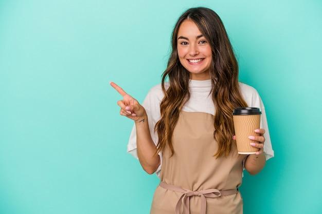 Jeune femme de commis de magasin caucasien tenant un café à emporter isolé sur fond bleu souriant et pointant de côté, montrant quelque chose dans un espace vide.