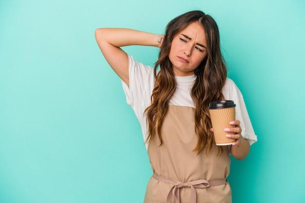 Jeune femme de commis de magasin caucasien tenant un café à emporter isolé sur fond bleu touchant l'arrière de la tête, pensant et faisant un choix.
