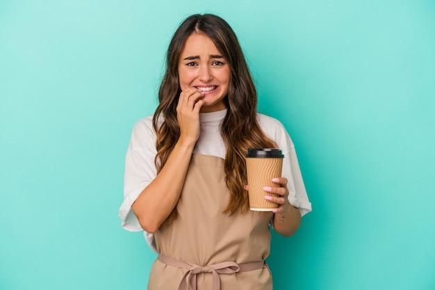 Jeune femme de commis de magasin caucasienne tenant un café à emporter isolé sur fond bleu se rongeant les ongles, nerveuse et très anxieuse.