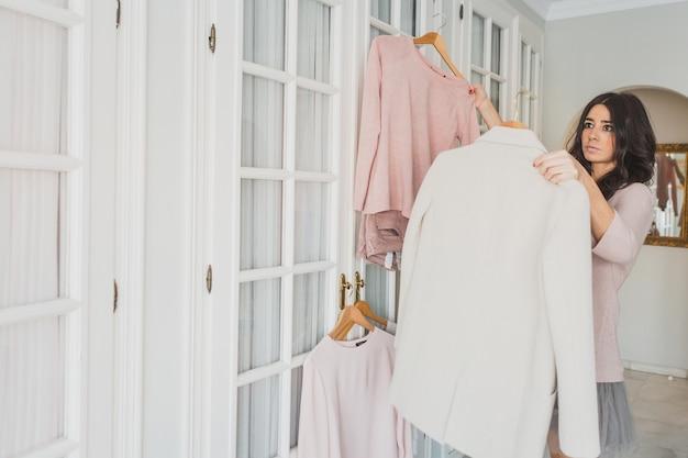 Jeune femme comparant différents vêtements