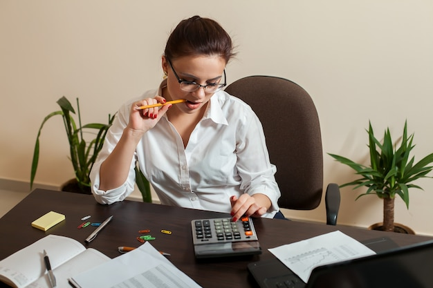 Jeune femme comptable considère sur la calculatrice