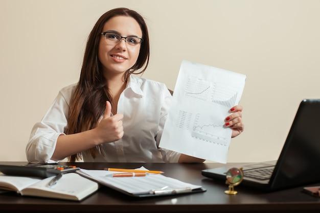 Jeune femme comptable montre les pouces vers le haut