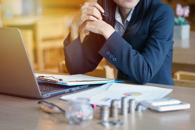 Jeune femme comptable utiliser la calculatrice. les jeunes employés de banque calculent des comptes.