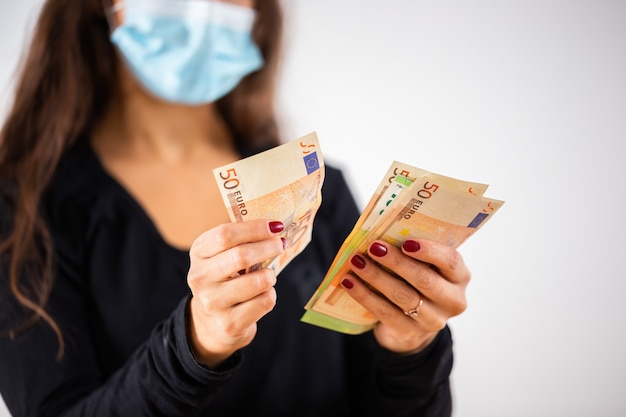 Jeune femme comptant de l'argent et portant un masque chirurgical bleu