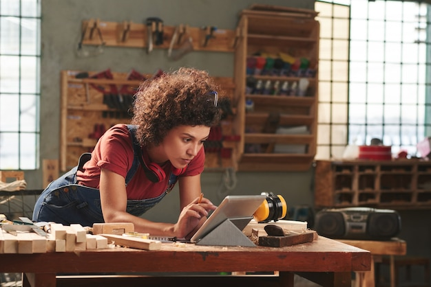 Jeune femme concentrée aux cheveux bouclés, lire les instructions sur tablette numérique avant de travailler avec du bois
