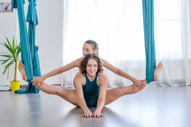 Jeune femme concentrée faisant du yoga antigravité à l'aide d'un hamac avec l'aide d'un entraîneur personnel