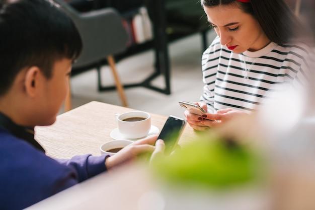 Jeune femme concentrée et un homme en face d'elle à la table assis et semblant concentrés tout en utilisant leurs smartphones