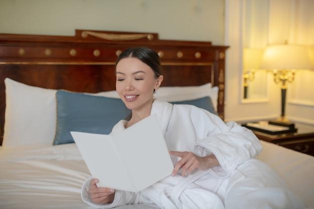 Une jeune femme concentrée reding un livre dans son lit