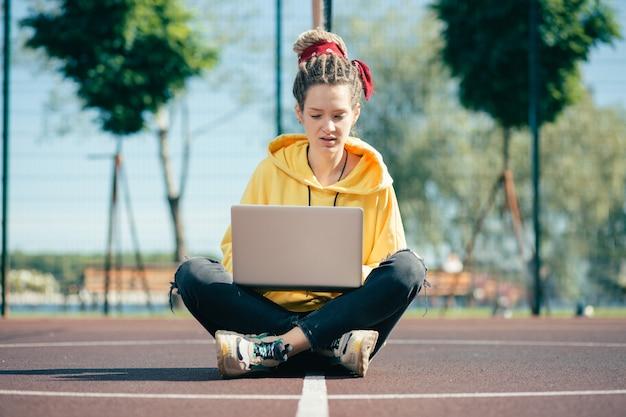 Jeune femme concentrée regardant pensivement l'écran de son ordinateur portable assis au milieu d'un terrain de sport
