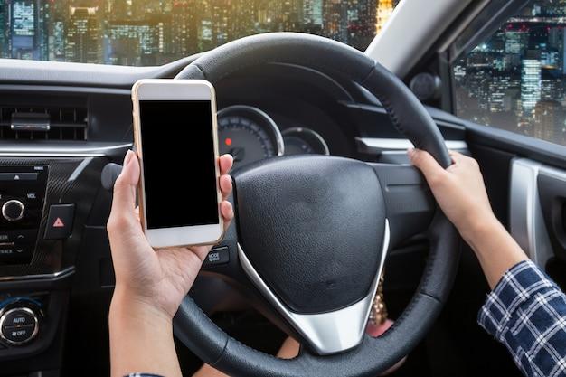 Jeune femme, conducteur, utilisation, écran tactile, smartphone, et, main, tenue, volant, dans, a, voiture