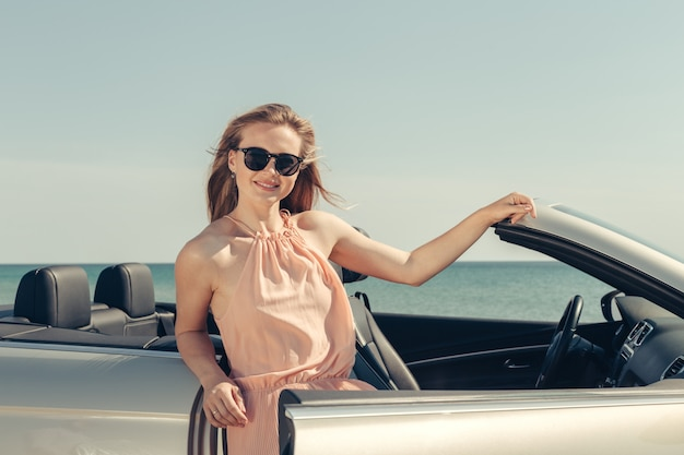 Jeune femme conduire une voiture sur la plage