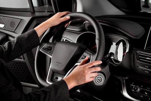 Jeune femme conduisant à l'intérieur d'une voiture de luxe, tenant le volant