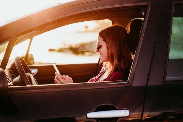 Jeune femme conduisant une voiture au coucher du soleil et à l'aide de téléphone portable. concept de voyage
