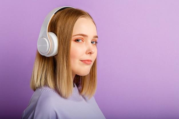 Jeune femme confiante en portrait d'écouteurs. belle femme sérieuse avec une coiffure blonde apprécie d'écouter de la musique de chanson dans un casque isolé sur un mur de couleur violette. espace de copie.