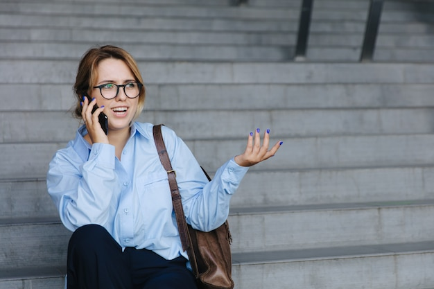 Jeune femme confuse assise à l'extérieur et parlant sur smartphone. dame séduisante à lunettes et tenue décontractée ayant une conversation mobile.