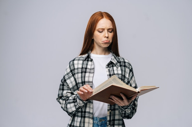 Jeune femme confuse étudiante tournant les pages du livre sur fond isolé gris