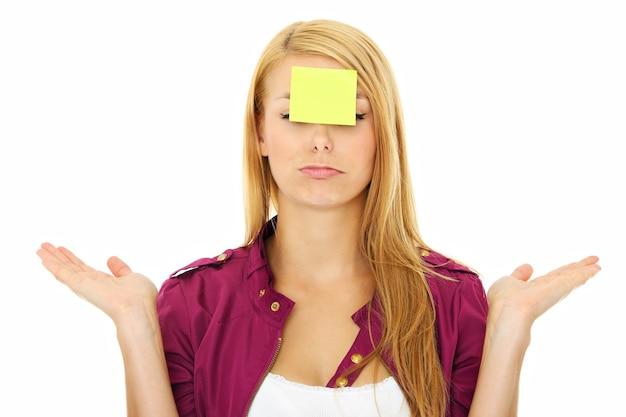 Une jeune femme confuse avec une note collante sur son front
