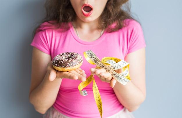 Jeune femme confuse tenant un beignet et un ruban à mesurer. concept de bonbons, malbouffe malsaine et obésité.