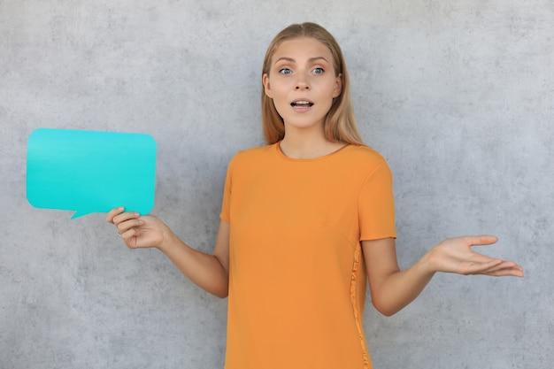 Jeune femme confuse tenant une bulle de dialogue vide isolée sur fond gris.