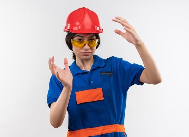 Jeune femme de constructeur mécontente en uniforme avec des lunettes faisant semblant de tenir quelque chose