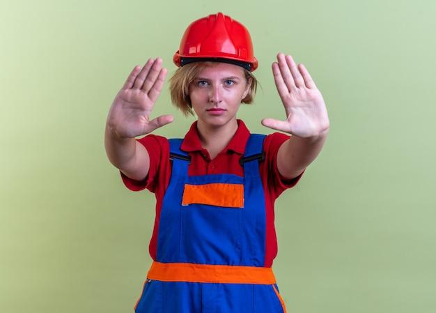 Jeune femme de constructeur stricte en uniforme montrant un geste d'arrêt isolé sur un mur vert olive