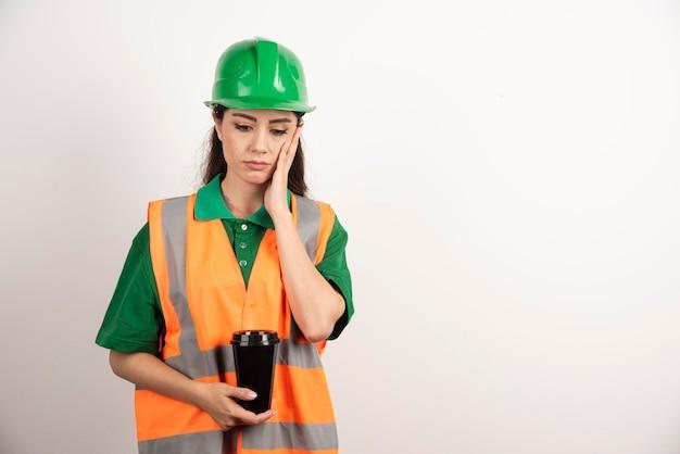 Jeune femme constructeur tenant une tasse noire. photo de haute qualité