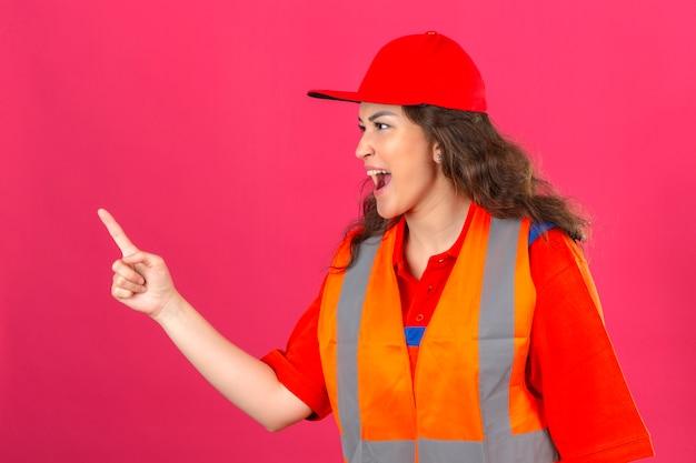 Jeune femme constructeur en uniforme de construction et casque de sécurité accusant quelqu'un sur mur rose isolé
